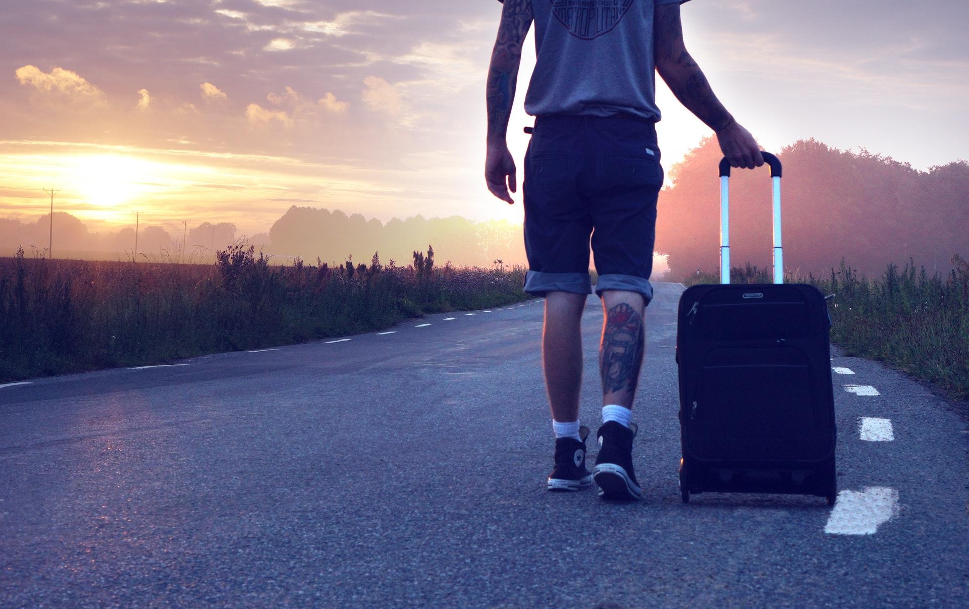 Homem na estrada com uma mala de viagem
