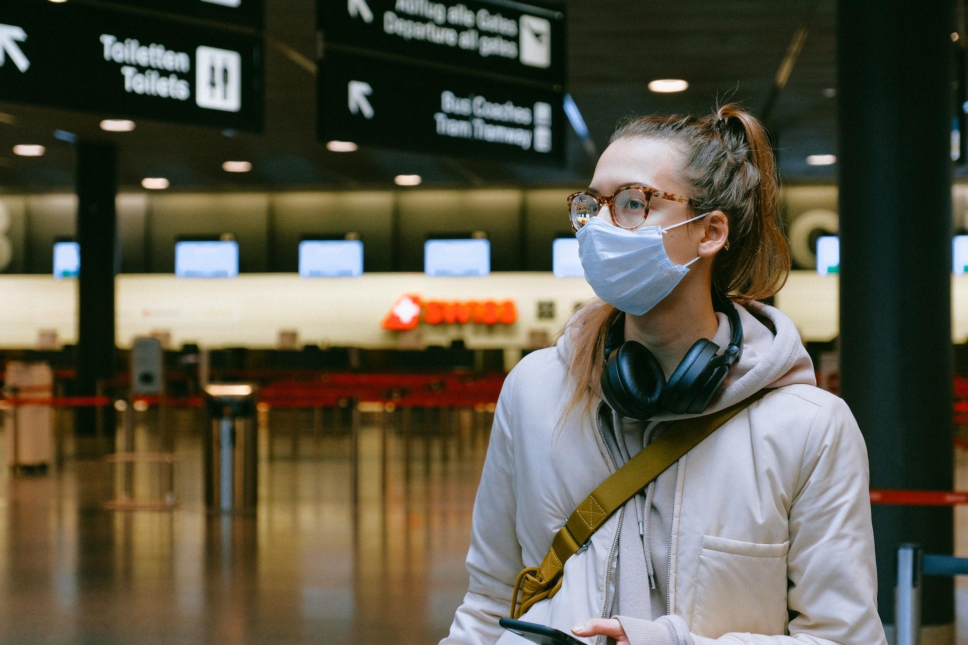Menina no aeroporto usando máscara