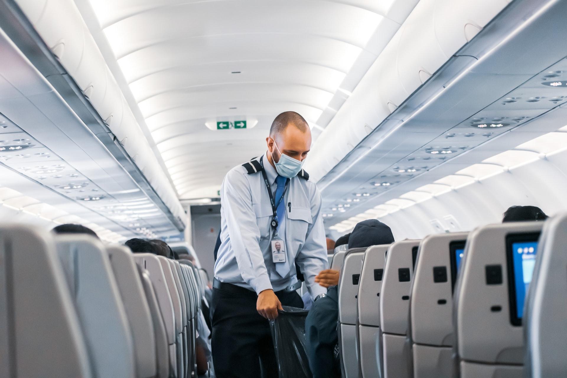 Comissário de bordo com máscara em viagem na pandemia